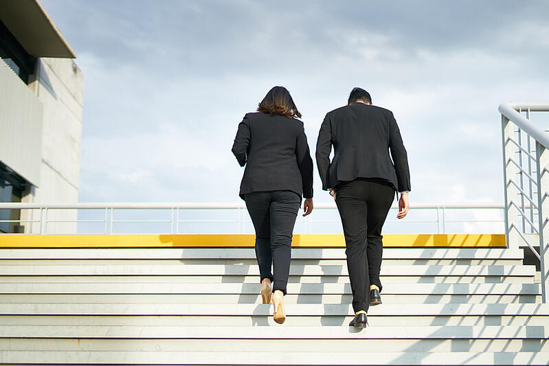 two-colleagues-walk-up-stairs-outside-employee-development