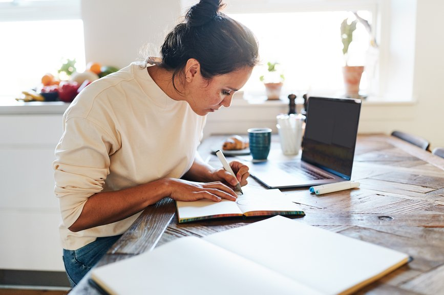 woman-journaling-at-her-desk-manage-your-energy-not-your-time