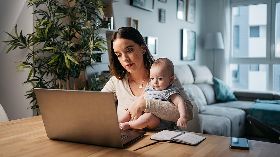 woman-balances-baby-arm-while-frowning-at-laptop-work-life-balance-main-image