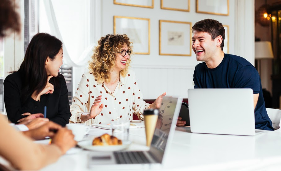 group-of-employees-sitting-at-a-table-laughing-stress-management-at-work