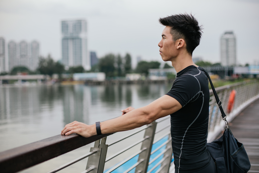 asian-athlete-in-black-meditating-by-water
