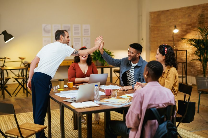colleagues-sitting-around-a-table-and-the-other-two-high-five-work-motivation