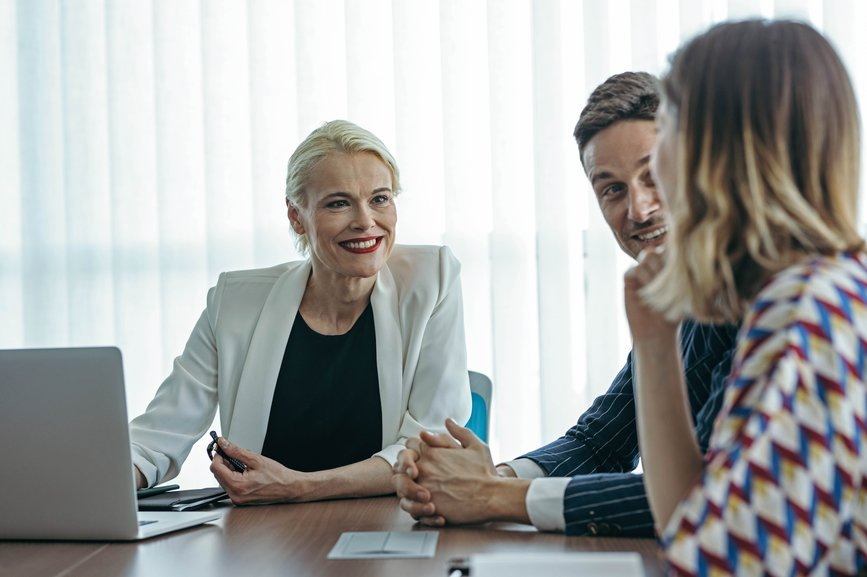 female-leader-sitting-at-meeting room-and-talking-with-her-employees-values-of-a-leader