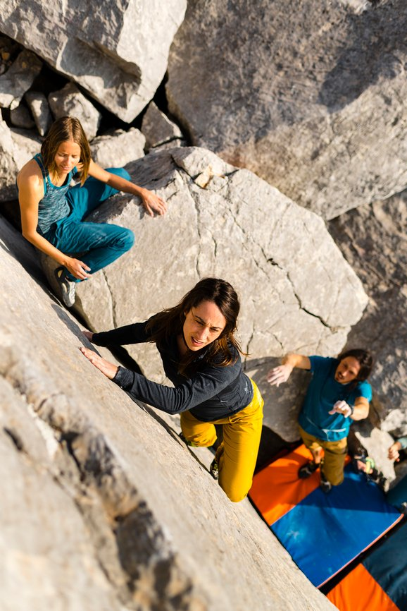 woman-climing-rock-with-2-others-supporting-from-below-empowerment-at-work