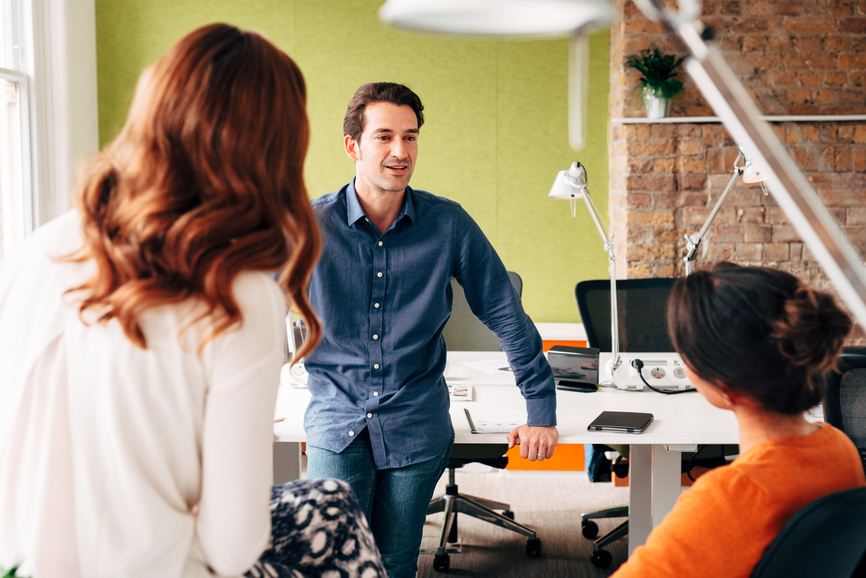 man-leaning-on-table-talking-to-colleagues-empowerment-at-work