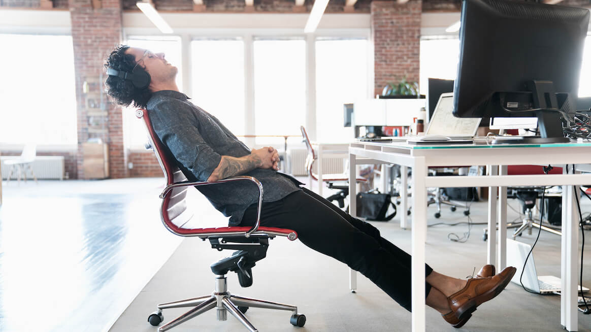 signs-of-burnout-leaning-away-from-desk-at-work
