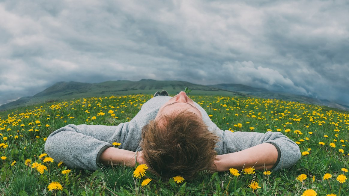 person-relaxing-in-field-of-flowers-types-of-rest
