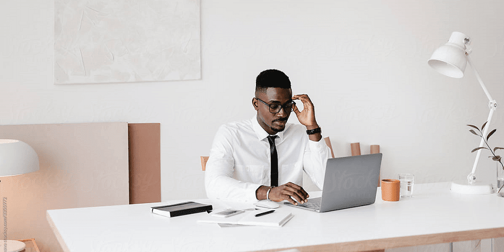 man-wearing-glasses-sitting-at-a-desk-working-on-a-laptop-in-an-office-full-potential