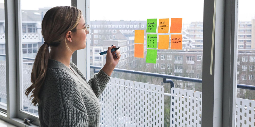 Woman-writing-on-sticky-notes-how-to-set-goals-and-achieve-them