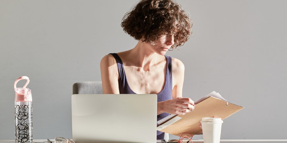 woman looking through paper - spiritual wellness