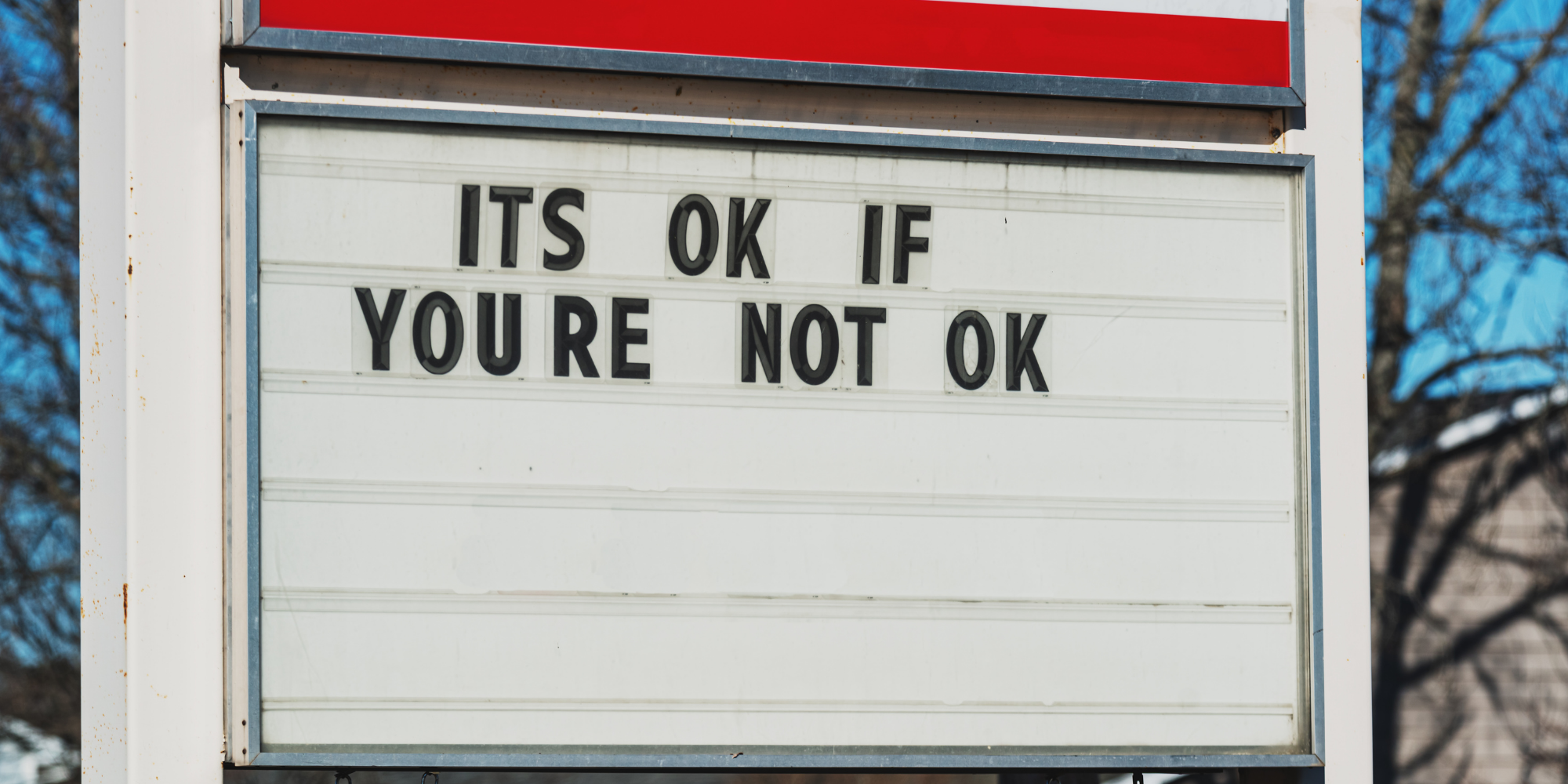 """sign board with the message """"it's okay if you're not okay"""""""