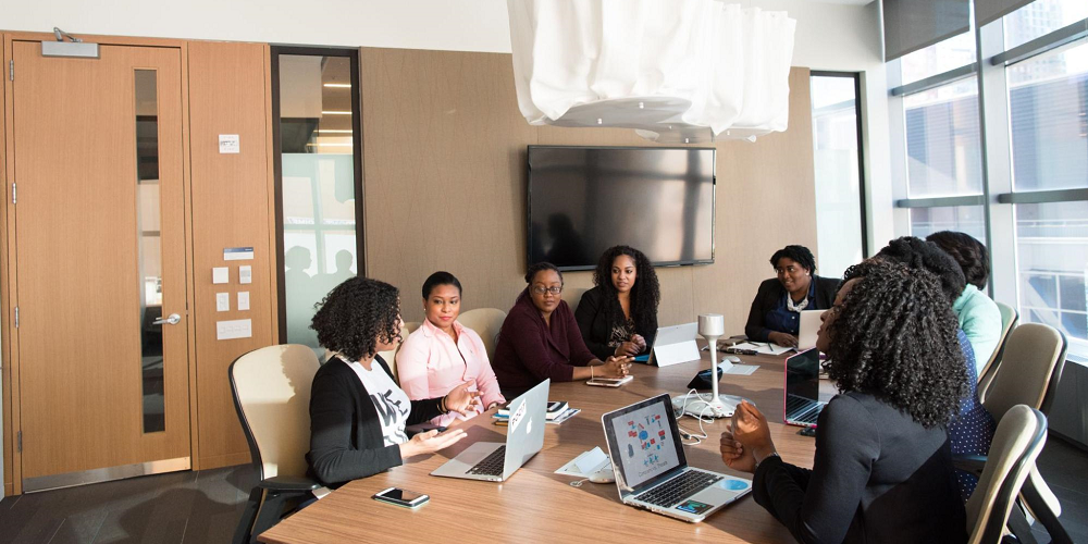 group-of-women-sit-around-table-in-office-employee-resource-group
