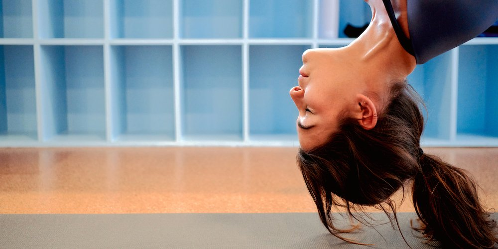 A woman smiling as she meditates upside-down