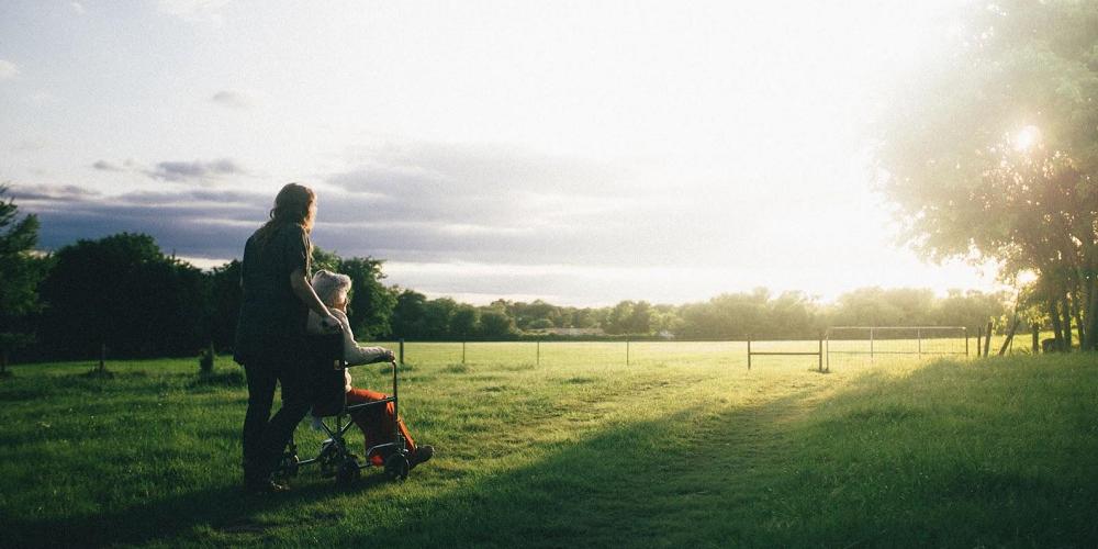 woman-pushing-elderly-in-a-wheelchair