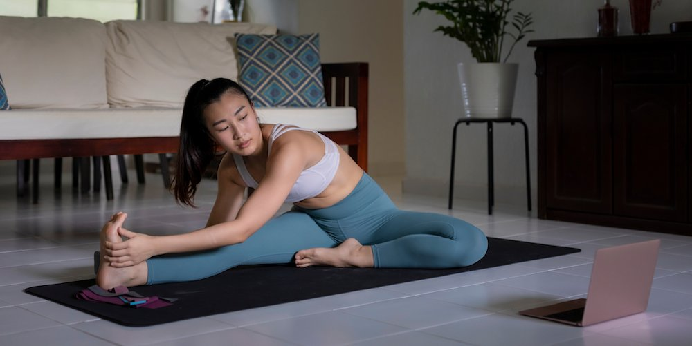 A woman participates in a virtual yoga class from home